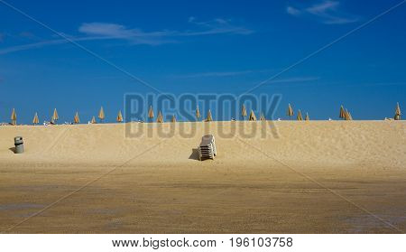 Many beach umbrella and chair on horizon line. Closed beach parasol on sky background