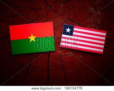 Burkina Faso Flag With Liberian Flag On A Tree Stump Isolated