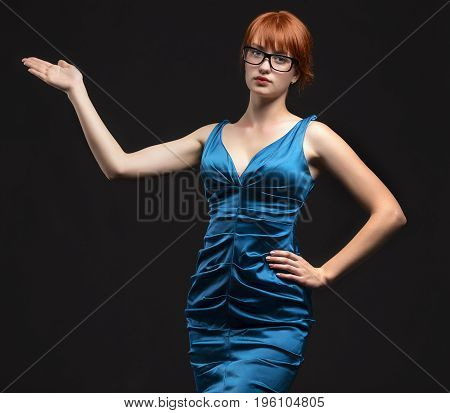 Young confident woman showing by hands on a black background. Ideal for banners, registration forms, presentation, landings, presenting concept.
