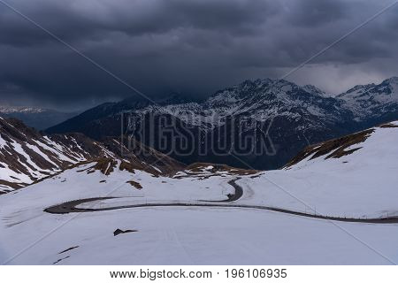 A landscape view from Hochtor tunnel on the Grossglockner high alpine road. Looking towards Heiligenblut in Carinthia with blue sky, mountains clouds and snow and the Grossglockner high alpine road.