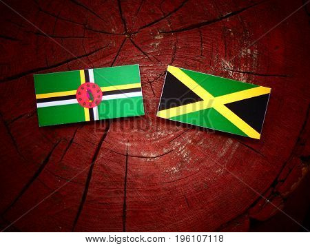 Dominica Flag With Jamaican Flag On A Tree Stump Isolated