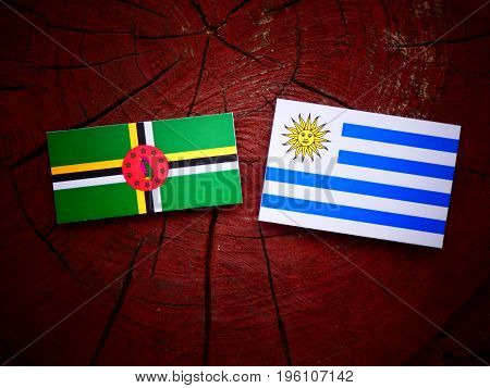 Dominica Flag With Uruguaian Flag On A Tree Stump Isolated