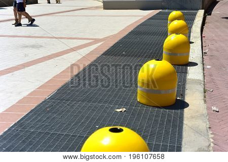 Five roadblocks yellow over the sidewalk in the background some people cross the sidewalk