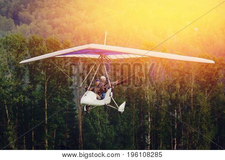 paraglider with pilot and passenger flies against background of forest and sunset, sunlight. concept is active extreme rest in open space.