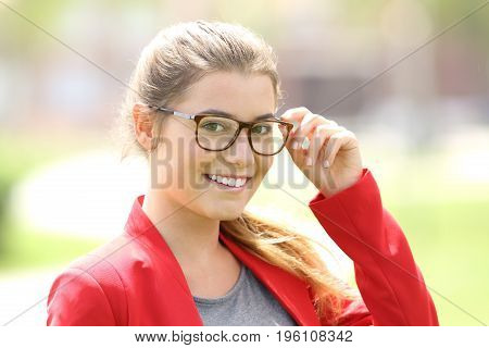 Fashion girl posing looking at you wearing eyeglasses outdoors in a park