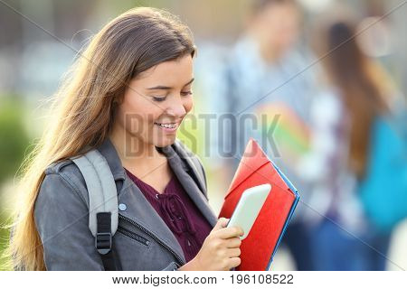 Single student checking smart phone and walking in the street
