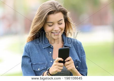 Portrait of a happy teen walking and reading text in a smart phone in the street