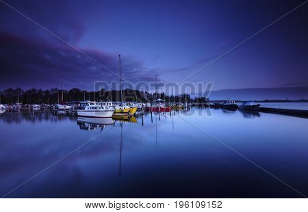 Small and colorful yachts at a platform reflected in a calm lake under a blue dawn