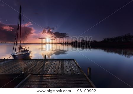 Sailboat tied to a wooden platform in a calm lake under a purple sunrise
