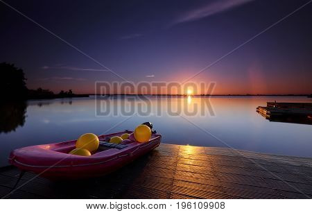 Small boat with coloured balls under a blue-orange sunrise at a quiet morning lake with sun rays and reflections