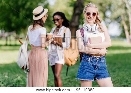 Beautiful Smiling Blonde Student With Headphones Holding Books While Friends Talking Behind In Park
