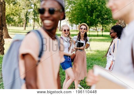 Laughing Multiethnic Girls In Sunglasses Looking At Boys Standing On Foreground