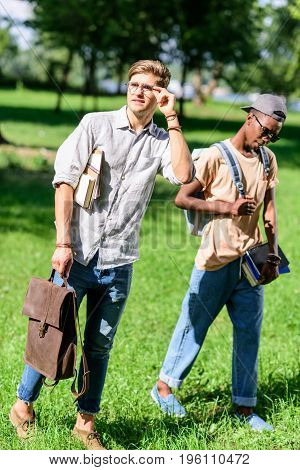 Stylish Young Multiethnic Men Holding Books And Backpack While Walking Together In Park