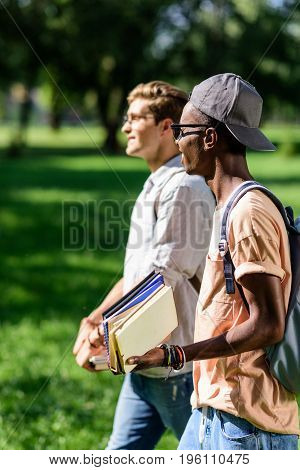 Side View Of Young Multiethnic Students Holding Books While Walking Together In Park