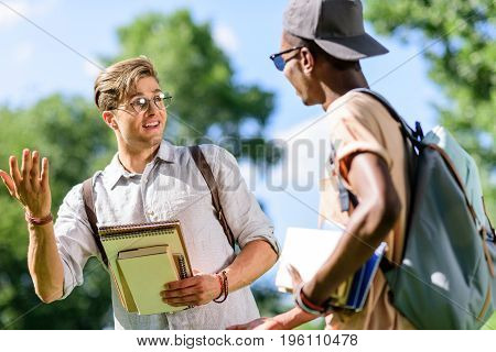 Smiling Young Multiethnic Students Holding Books And Talking In Park