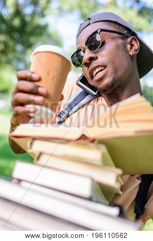 Young African American Man Talking On Smartphone While Holding Pile Of Books And Disposable Coffee C