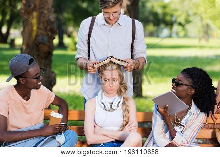 Young Multiethnic Group Of Students Sitting Together On Bench In Park