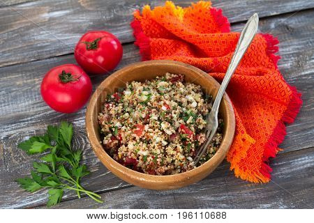 Peruvian salad with quinoa fresh greens and tomatoes. Delicious healthy vegetarian food. In a wooden bowl on a wooden background, selective focus
