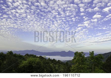 Sky background. Dramatic sunset cloudy sky with clouds lit by sunlight - natural sky background with colorful sky and clouds. Natural sky landscape. Slightly clouds floating on graduated blue sky with sunlight