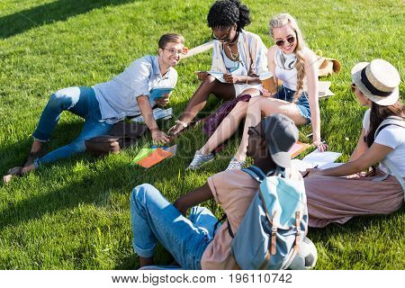 Smiling Young Multiethnic Students Talking And Reading Books While Resting On Grass In Park