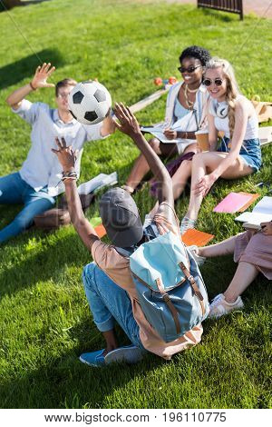 Happy Young Multiethnic Students Playing With Soccer Ball While Studying In Park