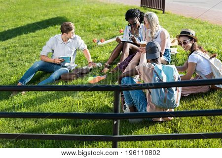 Smiling Young Multiethnic Students Reading Books While Resting On Grass In Park