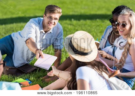 smiling young man giving blank notebook to girl in straw hat while laughing friends sitting on green grass