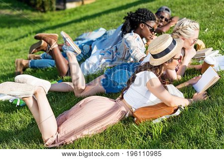 Young Multiethnic Students Reading Books While Lying On Grass And Studying In Park