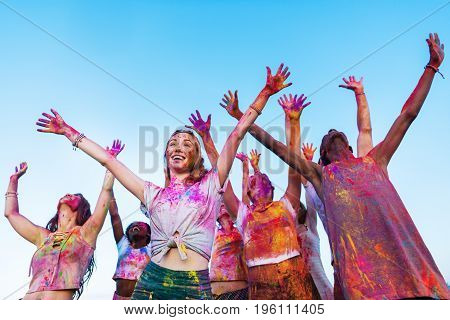 happy young friends with outstretched hands having fun together at holi festival