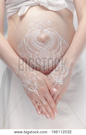 Pregnant belly closeup with white henna painting in boho style. Hands of mother under the belly