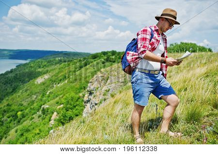 Stylish Man Wearing Checkered Red Shirt And A Hat Posing With A Map In The Nature With A Lake On The