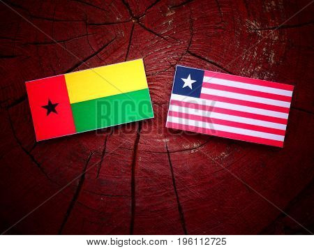 Guinea Bissau Flag With Liberian Flag On A Tree Stump Isolated