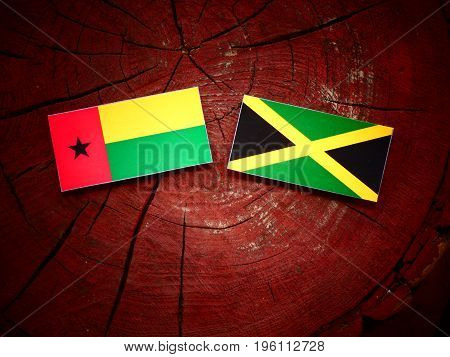 Guinea Bissau Flag With Jamaican Flag On A Tree Stump Isolated