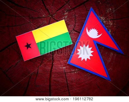 Guinea Bissau Flag With Nepali Flag On A Tree Stump Isolated
