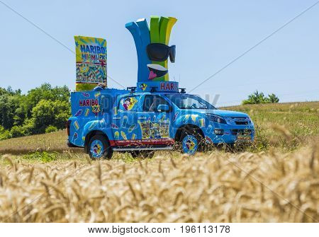 Saint-Quentin-Fallavier France - July 16 2016: Haribo vehicle during the passing of Publicity Caravan in a wheat plain in the stage 14 of Tour de France 2016. Haribo is the biggest manufacturer of gummy and jelly sweets in the world.