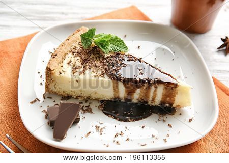 Plate with delicious cheesecake and chocolate on orange napkin