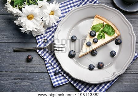 Plate with delicious cheesecake, berries and fork on wooden table