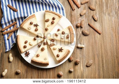 Delicious sliced cheesecake with nuts on wooden table