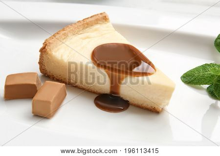 Plate with delicious cheesecake and caramel sauce, closeup