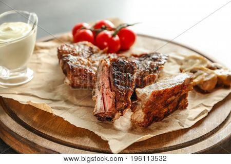 Yummy grilled spare ribs with mushrooms and cherry tomatoes on wooden board