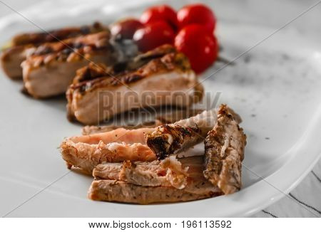 Yummy grilled spare ribs with cherry tomatoes on square white plate