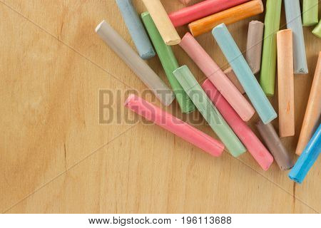 Group colored pastel chalks in a chaotic manner on a wooden background