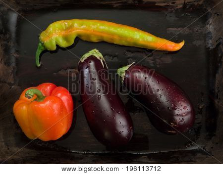 Eggplants hot peppers and sweet peppers On a wooden tray