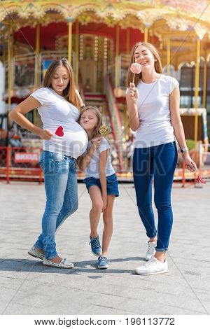 Samesex lesbian family with child on a walk in the amusement park. Lesbians mothers with adopted child, happy family, pregnant couple with kid