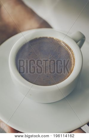 Closeup of tasty coffee espresso with tasty foam in small ceramic cup. Male hands holding warm hot drink.