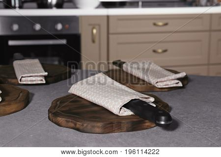 Knife with napkin and wooden board on kitchen table. Cooking classes concept