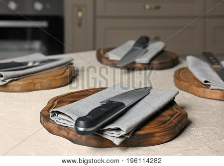 Knives with napkins and wooden boards on kitchen table. Cooking classes concept