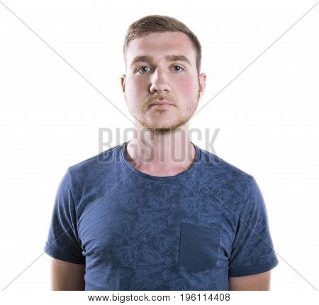 A neutral man with dark blonde hair isolated over the white background. A young male standing in a dark blue saturated t-shirt. A pessimistic stressed man with depression.