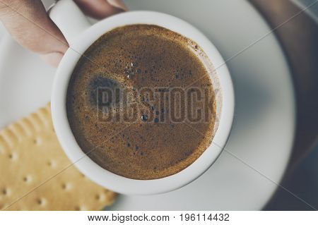 Closeup of tasty coffee espresso with tasty foam in small ceramic cup. Female hands holding warm hot drink.
