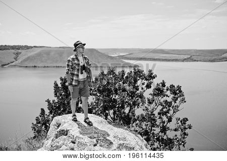 Portrait Of A Handsome Man In Checkered Shirt Posing With Binoculars. Black And White Photo.